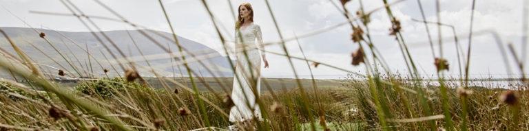 Braut in einem Hochzeitskleid auf einer grünen Wiese