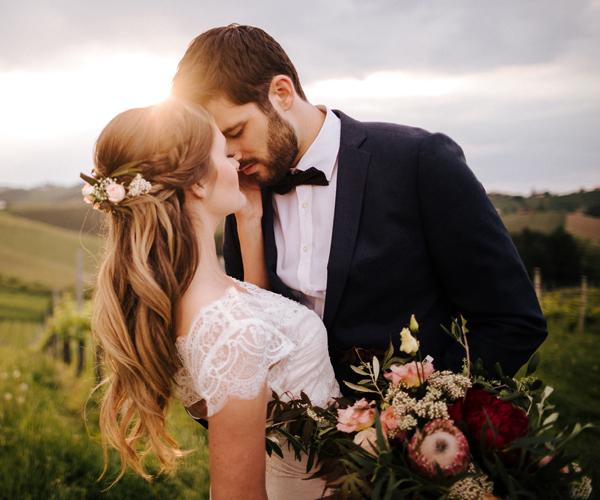 Brautpaar küsst sich bei Sonnenuntergang in den Weinbergen