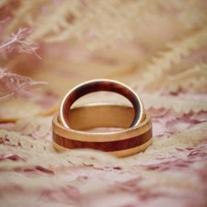 handgefertigte Eheringe aus Mittelgold in Kombination mit Wüsteneisenholz und eismatter Oberfläche