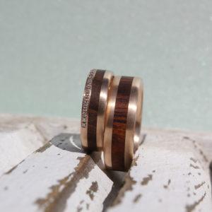 handgefertigte Eheringe aus Mittelgold in Kombination mit Wüsteneisenholz und eingefassten Brillanten